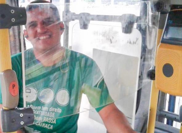 Cobrador sentado, no interior de um ônibus protegido por película