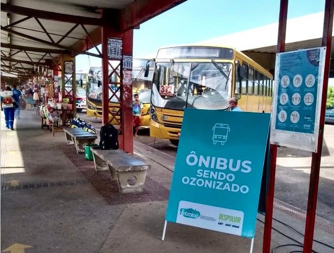 """Parte coberta de terminal de integração com cavalete """"ônibus sendo ozonizado"""""""